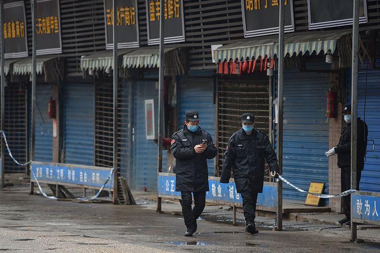 Petugas keamanan berpatroli di pasar ikan tradisional Huanan di kota Wuhan, China, Jumat (24/1/2020). Pasar ikan itu ditutup setelah virus corona yang mematikan dideteksi berasal dari pasar itu.