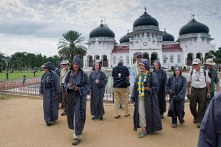 Turis dari kapal pesiar MV Clipper Odyssey mengenakan pakaian khusus saat memasuki kompleks Masjid Raya Baiturrahman, Banda Aceh, Kamis (10/1/2013). Kapal yang mengangkut 150 penumpang dari berbagai negara dalam tour wisata Zegrahm Expedition tersebut melego jangkar selama enam jam di lepas pantai Banda Aceh untuk membawa para turis melakukan city tour ke beberapa situs sejarah dan tsunami Aceh.