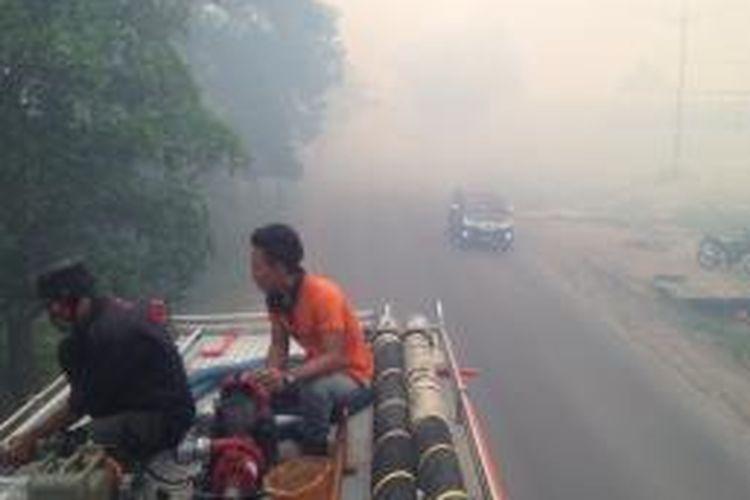 Petugas dari Manggala Agni sedang mengoperasikan pompa air di mobil pemadam kebakaran untuk memadamkan api di Jalan Mahir Mahar, Palangkaraya, Kalteng, Minggu (14/9) sore. Asap pekat mengganggu pengendara dan mengakibatkan kabut asap hingga malam hari.