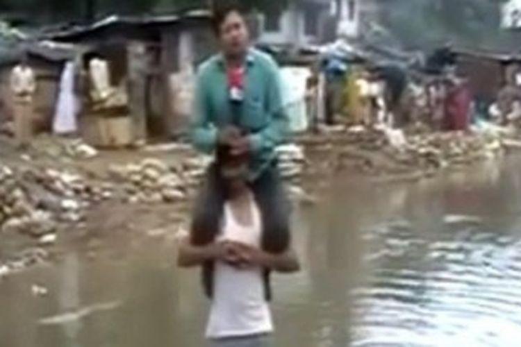 Foto ini diambil dari video yang diunggah ke situs YouTube menampilkan saat seorang wartawan televisi India digendong seorang korban banjir saat melaporkan berita untuk stasiun televisi tempatnya bekerja.