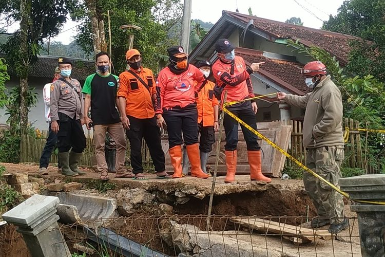 Personnel of the Sukabumi Disaster Mitigation Agency (BPBD) and volunteers visit the cracked land that has reportedly expanded in Ciherang, Nyalindung district in Sukabumi Regency, West Java on Saturday, February 2, 2021.