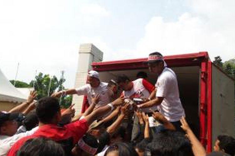 Relawan Jokowi saat membagi-bagikan buku, jelang konser Salam 2 Jari, di Stadion Gelora Bung Karno, Sabtu (5/7/2014)