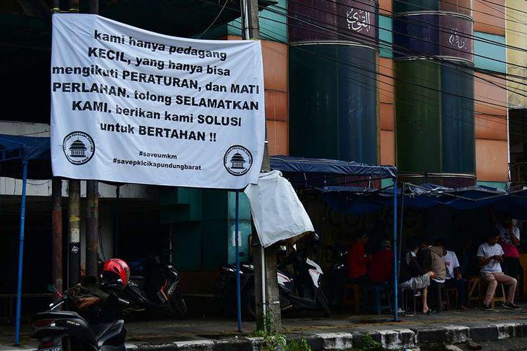 Pedagang kaki lima (PKL) yang berada di Jalan Cikapundung Barat, Kota Bandung, Jawa Barat, melakukan aksi pasang bendera putih di kios mereka, menyusul pemberlakuan PPKM Darurat, Senin (19/7/2021). Bendera putih yang dikibarkan 104 pedagang itu merupakan tanda mereka tak lagi sanggup menghadapi Covid-19 yang telah menghancurkan perekonomian.