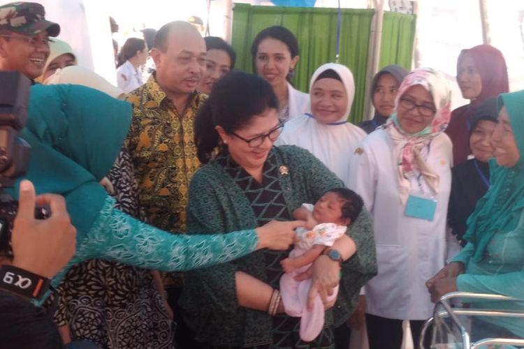 Menteri Kesehatan Nila Djuwita Moeloek menggendong seorang bayi pengungsi di rumah sakit darurat dr Ishak Umarela, Desa Tulehu, Kecamatan Salahutu, Kabupaten Maluku Tengah, Rabu (16/10/2019).