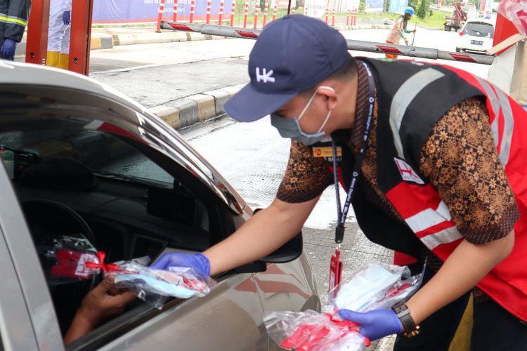 Pemberian masker gratis yang dilakukan oleh petugas dengan pengguna jalan tol.