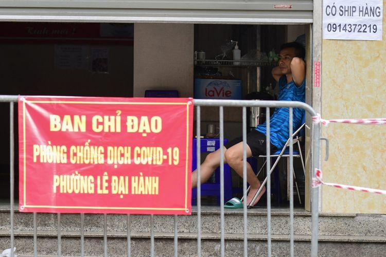 Seorang pria duduk di depan restoran yang tutup akibat lockdown untuk menghentikan penyebaran Covid-19 di Hanoi, 12 Juli 2021.