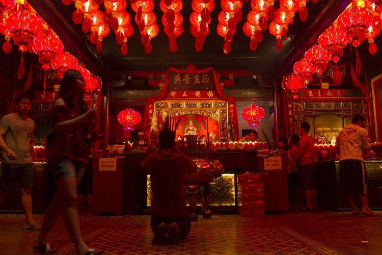 Sejumlah warga Tionghoa melakukan sembahyang di malam Imlek di Vihara Dhanagun, Kota Bogor, Jawa Barat, Jumat (24/1/2020). Usai memanjatkan doa warga Tionghoa menyalakan lilin yang disusun di halaman vihara.