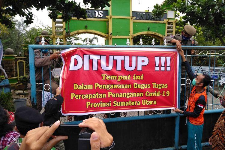 "Menjelang tengah hari, Tim Gugus Tugas memasng spanduk penutupan di pintu gerbang masuk ke Hairos Water Park. Spanduk tersebut bertuliskan ""Ditutup!!!  Tempat ini Dalam Pengawasan Gugus Tugas Percepatan Penanganan Covid-19 Sumatera Utara"". Pemasangan spanduk tersebut perhatian warga sekitar dan mengakibatkan kemacetan."