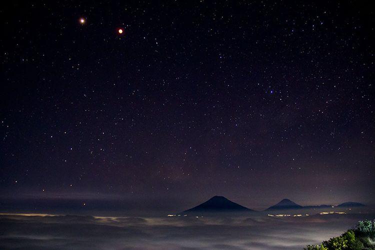 Pesona keindahan malam di langit barat Gunung Andong meliputi gerhana bulan dan planet mars, gemerlap bintang, dan Gunung Sindoro, Sumbing, serta Prau