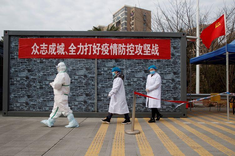 Staf medis dengan pakaian lengkap berjalan di pos pemeriksaan zona eksklusi Jembatan Sungai Yangtze di Jiujiang, Provinsi Hubei, pada 1 Februari 2020 di tengah merebaknya virus corona.