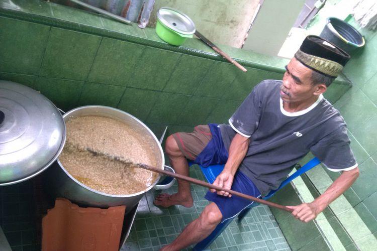 Kartibi juru masak bubur suro, saat mengaduk bubur untuk dibagikan kepada warga dan jamaah masjid Suro Palembang, Sumatera Selatan