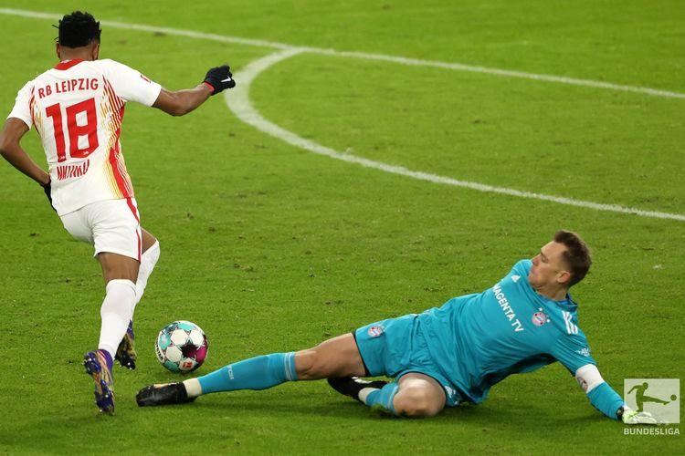 Penyerang RB Leipzig, Christopher Nkunku (kiri), melewati hadangan kiper Bayern Muenchen, Manuel Neuer, dalam pertandingan pekan ke-10 Bundesliga di Allianz Arena, Muenchen, Sabtu (5/12/2020). Gol pemain nomor punggung 18 ini membuat RB Leipzig memimpin 1-0 atas tuan rumah.