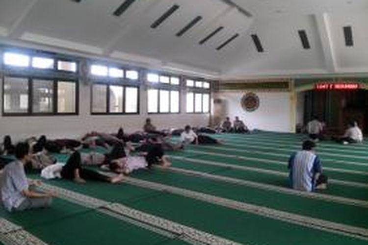 Usai melaksanakan salat zuhur, para pegawai tidur-tiduran di dalam masjid.