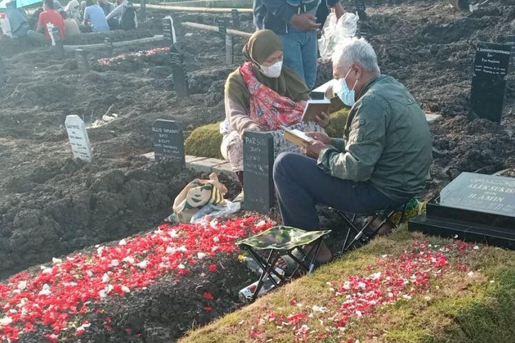 Dua orang peziarah yang sedang membacakan doa di salah satu makam di Tempat Pemakaman Umum (TPU) Selapajang, Neglasari, Kota Tangerang, Minggu (11/4/2021)