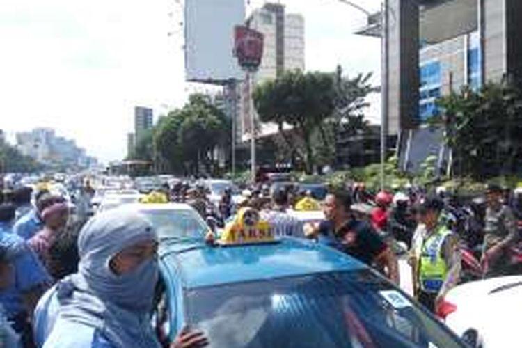 Suasana di Jalan Gatot Soebroto, Jakarta Selatan saat para supir taksi menutup sebagian ruas jalan tersebut pada Selasa (22/3/2016).