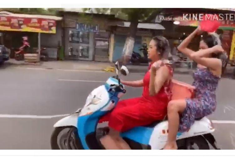 Tangkapan layar dari video aksi mandi keramas diatas motor yang sedang melaju di jalan raya, yang dilakukan 2 wanita di Mojokerto, Jawa Timur.