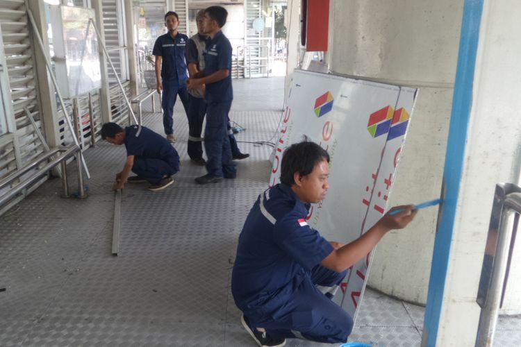 Petugas dari PT Transjakarta, Jumat (26/5/2017), mulai memperbaiki Halte transjakarta Kampung Melayu yang rusak akibat ledakan bom pada Rabu malam lalu.