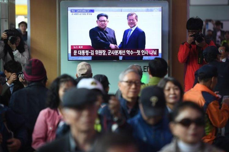 Masyarakat menyaksikan layar televisi yang memperlihatkan cuplikan langsung pertemuan Presiden Korea Selatan Moon Jae-in dan pemimpin Korea Utara Kim Jong Un, di sebuah stasiun kereta api di Seoul, Jumat (27/4/2018). (AFP/Jung Yeon-je)