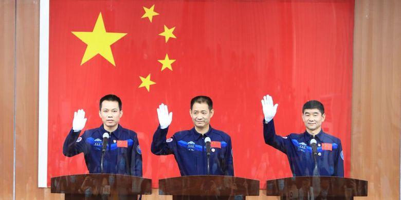 Tiga awak astronot misi Shenzhou 12 China yang dikirim ke stasiun luar angkasa baru, Tianhe, melambai kepada wartawan dalam konferensi pers di Pusat Peluncuran Satelit Jiuquan pada 16 Juni 2021. Mereka (dari kiri) adalah Tang Hongbo, Nie Haisheng, dan Liu Boming.