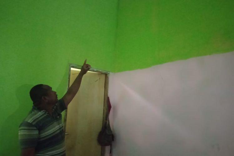 Kornelius Tosi, warga RT 6 RW 12 Desa Lifuleo, saat menujukan dinding rumahnya yang rusak akibat getaran ledakan pembangunan PLTU oleh PT Timor 1.