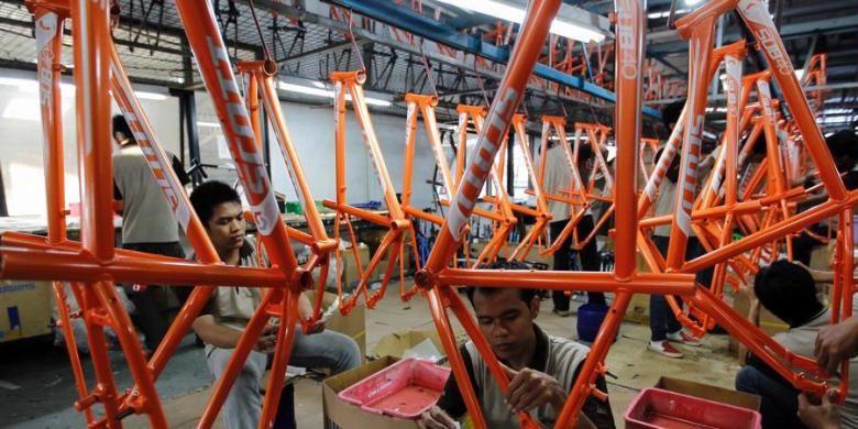 Pekerja memasang label di kerangka sepeda merek SCOTT di pabrik sepeda PT Insera Sena di Desa Wadungasih, Bunduran, Sidoarjo, Jawa Timur, beberapa waktu lalu.  Sebanyak 65 persen total produksi tersebut adalah sepeda merek SCOTT dan sejumlah merek lainnya yang diekspor untuk memenuhi pasar Eropa. Sedangkan untuk pasar lokal, pabrik ini membuat sepeda dengan merek di antaranya Polygon dan MUSTANG.