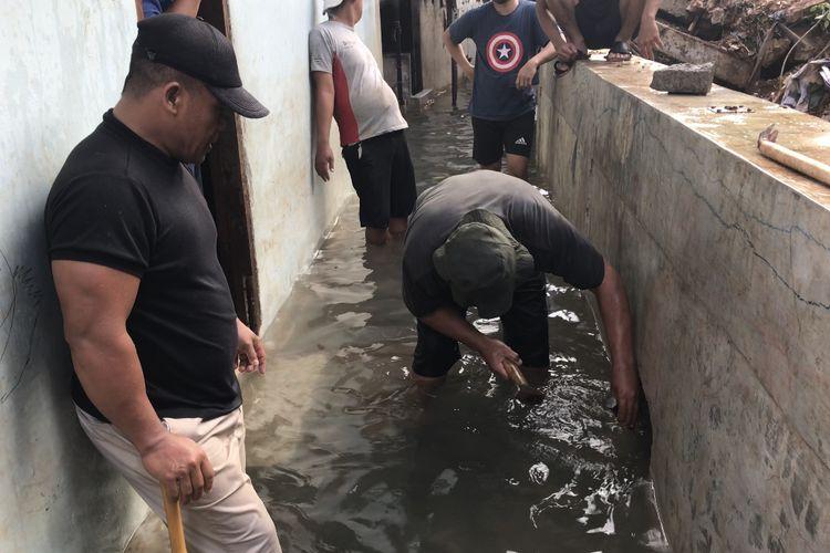 Sejumlah warga berinisiatif menangani banjir yang merendam wilayah pemukiman warga di Gang Melati RT 010 RW 03, Bangka, Mampang Prapatan, Jakarta Selatan pada Minggu (21/2/2021) sore.