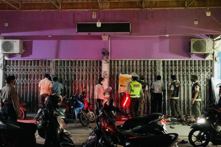 Tim gabungan saat menemukan sebuah toko pakaian di Jalan Kaharuddin Nasution, Kecamatan Bukitraya, Kota Pekanbaru, Riau, dengan pintu tertutup namun banyak warga berkerumun beli pakaian di dalamnya, Minggu (2/5/2021) malam.