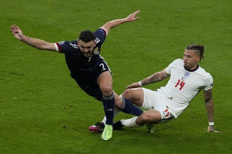 John McGinn (kiri) berduel dengan Kalvin Phillips (kanan) pada laga Grup D Euro 2020 yang mempertemukan Inggris vs Skotlandia di Stadion Wembley, Sabtu (19/6/2021) dini hari WIB.