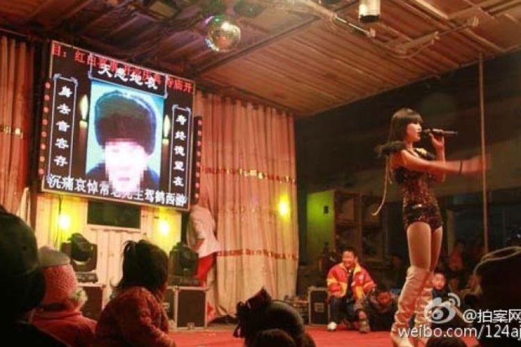 Seorang gadis tengah menghibur pada sebuah upacara pemakaman di China. Saat ini, pemerintah tengah getol memberantas fenomena striptis di upacara pemakaman karena dianggap tidak beradab.