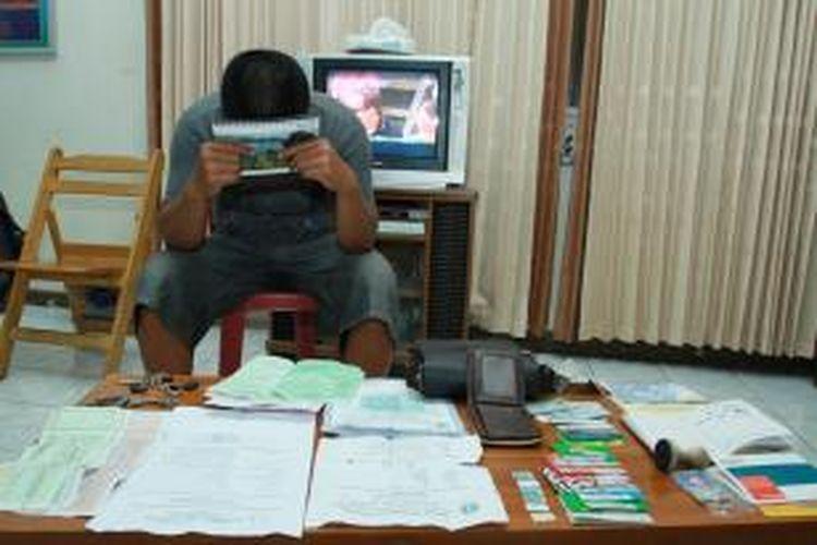 IJ dan barang bukti yang berhasil diamankan pihak kepolisian saat berada diruangan Kasat Reskrim Polres Singkawang, Kalimantan Barat (16/9/2013)