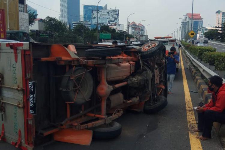 Sebuah mobil boks yang sedang melintas di ruas tol dalam kota kawasan Grogol, Jakarta Barat terguling pada Jumat (5/3/2021) siang, sekitar pukul 12.00 WIB.
