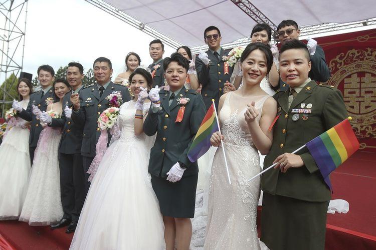 Dua pasangan lesbian, dari kanan ke kiri, Yi Wang dan Yumi Meng, Chen Ying-hsuan dan Li Li-chen berpose untuk foto saat upacara pernikahan massal militer di kota Taoyuan, Taiwan utara, Jumat, 30 Oktober 2020. Dua pasangan lesbian bersatu dalam ikatan sipil dalam upacara pernikahan massal yang diadakan oleh militer Taiwan pada hari Jumat dan merupakan sebuah langkah bersejarah. Taiwan adalah satu-satunya tempat di Asia yang melegalkan ikatan sipil sesama jenis, mengeluarkan UU terkait hal tersebut pada Mei 2019.