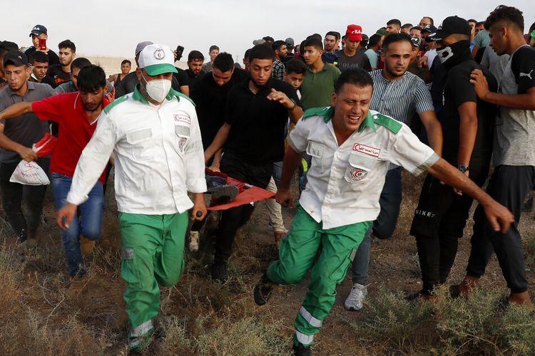 Petugas medis di sebelah timur Kota Gaza, Sabtu (21/8/2021), mengevakuasi orang yang terluka dari pagar perbatasan Jalur Gaza dengan Israel, selama protes menandai peringatan serangan pembakaran 1969 di masjid Al-Aqsa Yerusalem oleh seorang turis Australia yang kemudian diketahui sakit jiwa.