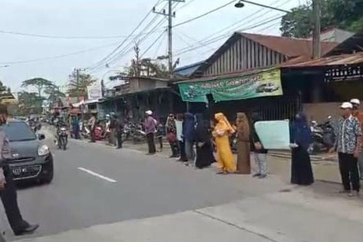 Warga berjejer di tepi jalan saat jenazah Sumadi dibawa menuju Tempat Pemakaman Umum (TMU) Raudhatul Jannah Serayu, Tanah Merah, Samarinda untuk penguburan sesuai protokol Covid-19, Minggu (30/8/2020).