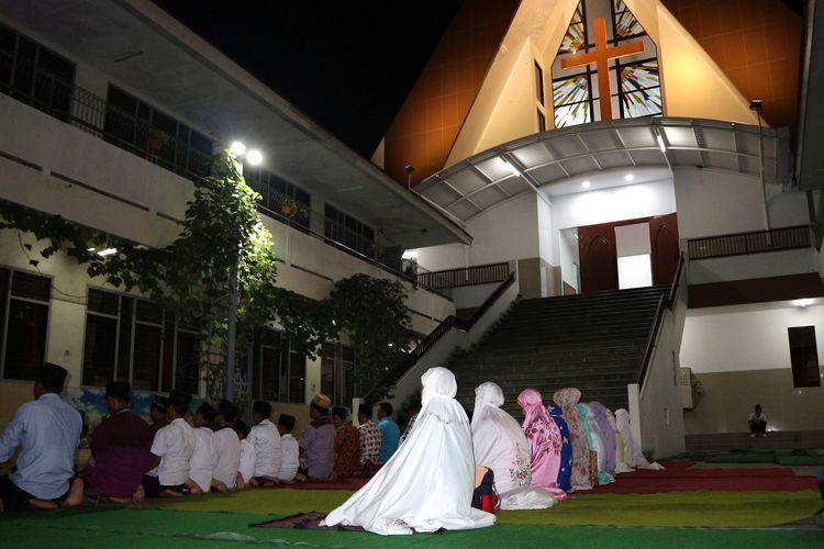 Para siswa dan guru MI Islamiyah menggelar shalat Maghrib di komplek SD Kristen Petra Jombang, (27/5/2019) malam.