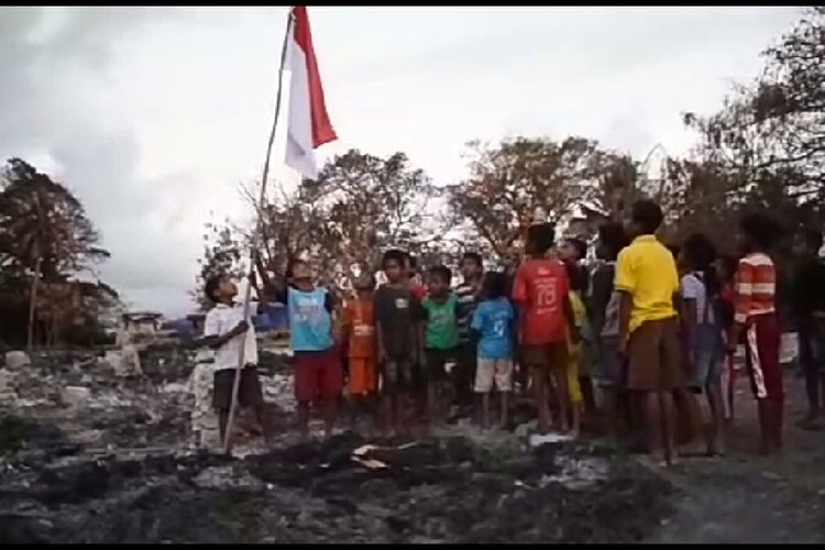 Anak-anak menancapkan tiang bendera dan memberikan hormat kepada Bendera Merah Putih di atas puing-puing rumah yang sudah hangus terbakar di Kampung Adat Situs Deke, Desa Patiala Bawah, Kecamatan Lamboya, Kabupaten Sumba Barat, Nusa Tenggara Timur (NTT).