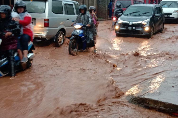 Banjir air bercampur tanah lumpur menutupi badan jalan provinsi di Jalan Simpang-Parakanmuncang, Cimanggung, Sumedang, Jawa Barat, Minggu (9/2/2020) siang. AAM AMINULLAH/KOMPAS.com