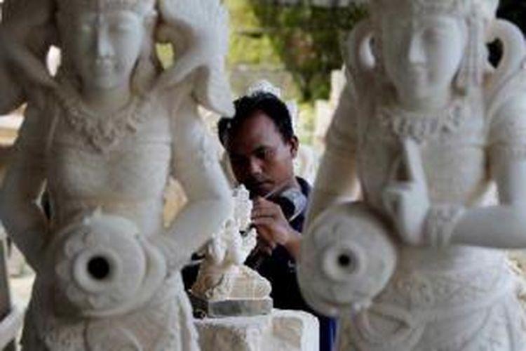 Perajin patung menyelesaikan pembuatan patung dari batu padas di Batubulan, Kecamatan Sukawati, Gianyar, Bali, Minggu (8/5/2011). Batubulan dan Singapadu di Kecamatan Sukawati menjadi sentra pembuatan patung khususnya dari bahan campuran semen dan batu paras serta batu padas. Patung-patung tersebut diekspor hingga ke mancanegara.