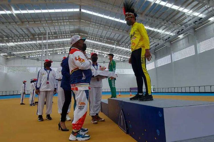 Pengalungan medali emas yang dilakukan Gubernur Papua, Lukas Enembe, kepada atlet Sepatu Roda Papua, Dave Emmanuel Abel, Jayapura, Papua, Senin (27/9/2021)