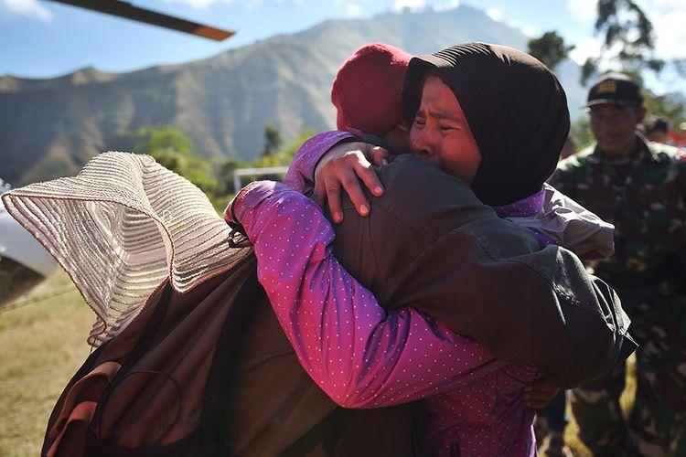 Pendaki Gunung Rinjani yang sempat terjebak longsor akibat gempa bumi, Suharti (kanan), berpelukan dengan adiknya setelah berhasil dievakuasi dan tiba di Lapangan Sembalun Lawang, Lombok Timur, NTB, Selasa (31/7/2018). Tiga orang pendaki yang terjebak akibat gempa berhasil dievakuasi menggunakan helikopter.