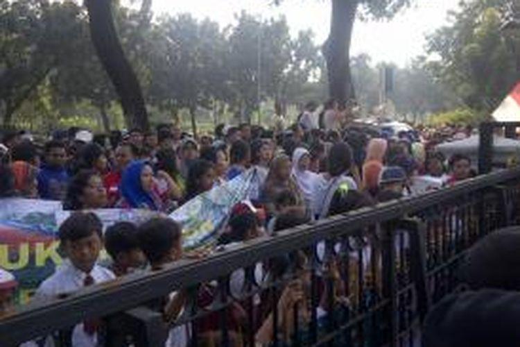 Puluhan siswa berseragam sekolah dasar (SD) ikut aksi unjuk rasa menolak pembongkaran bangunan liar di bantaran Kali Ciliwung, di depan Balai Kota, Jumat (22/5/2015).