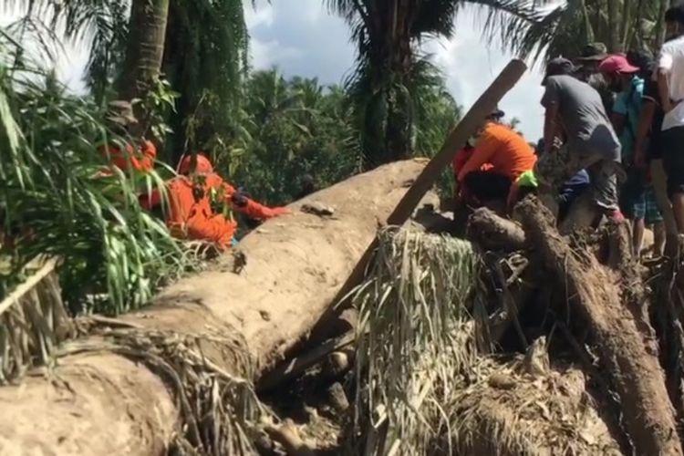 Korban banjir ditemukan di puing puing kayu bercampur lumpur di Desa Radda, Kecamatan Baebunta, Luwu Utara, Sabtu (18/07/2020)