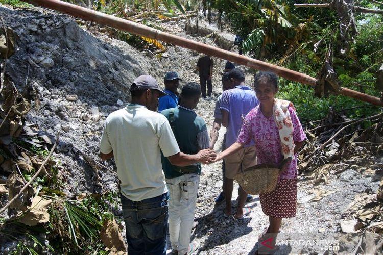 Warga Desa Tunbaun, Kecamatan Amarasi Barat, Kabupaten Kupang, Nusa Tenggara Timur melintas di lokasi longsoran, Selasa (13/4).