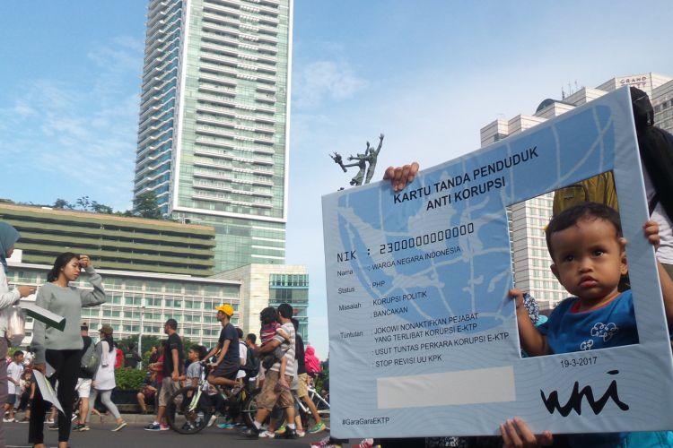 """Seorang balita tengah berpose dengan menggunakan alat peraga bertuliskan """"KTP Anti Korupsi"""" saat kegiatan car free day di Bundaran Hotel Indonesia, Minggu (19/3/2017). Sejumlah kelompok masyarakat menyerukan gerakan agar pemerintah serius mengusut kasus dugaan korupsi e-KTP hingga tuntas."""
