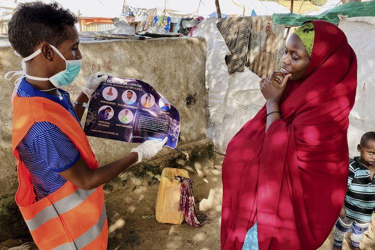Wanita penduduk migran di Somalia (kanan) saat menerima penyuluhan petugas tentang cara melindungi diri dari virus corona di kamp Weydow IDP, Mogadishu, Somalia. Foto diambil pada 10 Juni 2020.