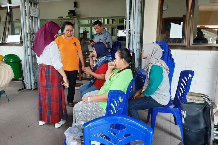 Salah satu karyawan (baju merah) pabrik garmen di daerah Kecamatan Ngaglik, Kabupaten Sleman duduk dikursi setelah mendapat perawatan di RS Panti Nugroho dan sudah diperbolehkan pulang.