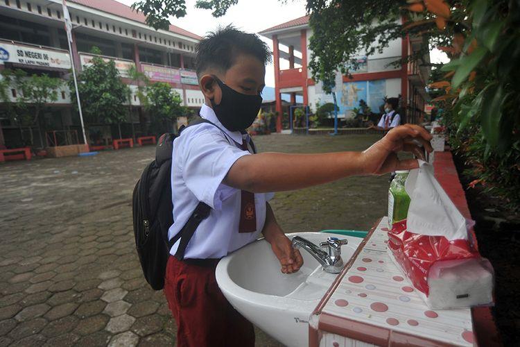 Seorang siswa mencuci tangan sebelum masuk ke kelas, di SDN 06 Lapai, Padang, Sumatera Barat, Senin (4/1/2021). Pemkot Padang membuka sekolah untuk belajar tatap muka dan wajib mengikuti protokol kesehatan Covid-19 dengan jumlah isi kelas hanya 50 persen, sebagian belajar daring di rumah.