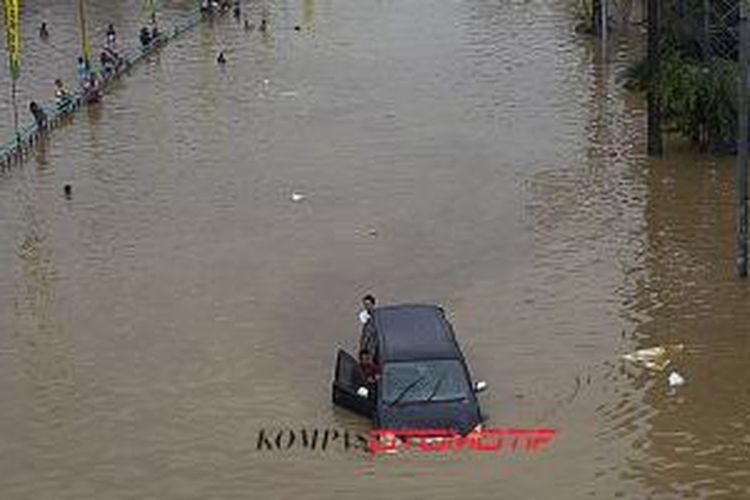Luapan Kali Ciliwung memutus jalur kendaraan di Jalan KH Abdullah Syafi'ie, Tebet, Jakarta Selatan, Senin (13/1/2014)