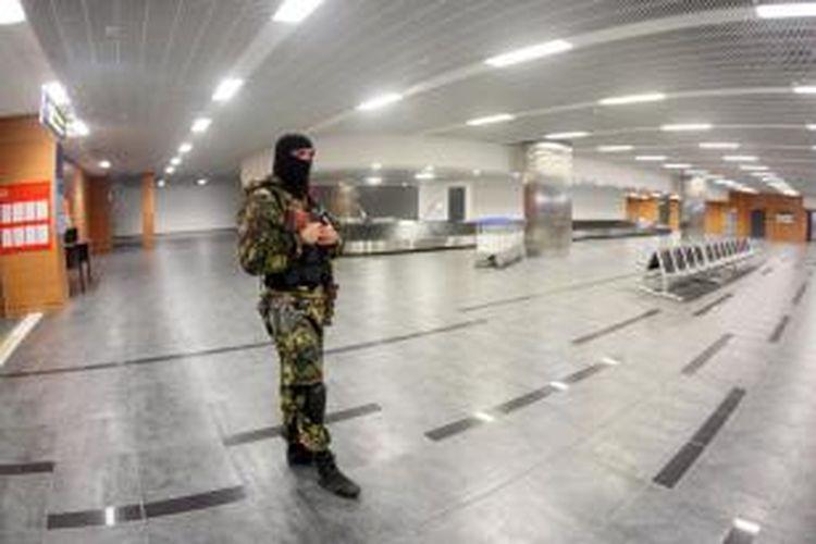 Seorang anggota milisi pro-Rusia berjaga di salah satu ruangan di bandara kota Donetsk, wilayah timur Ukraina yang mereka duduki.