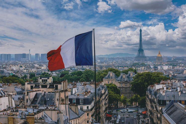 Bendera Prancis dengan latar belakang Menara Eiffel di Paris.